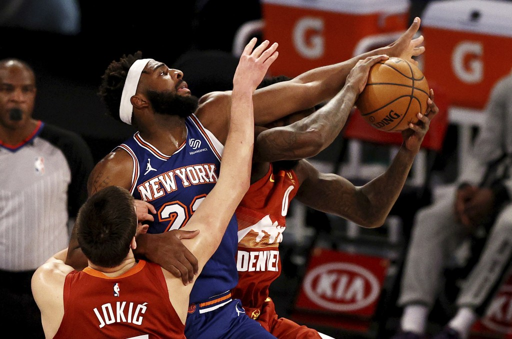 New York Knicks' Mitchell Robinson (23) defends against Denver Nuggets' Nikola Jokic as Nuggets' JaMychal Green (0) grabs a rebound during an NBA bask...