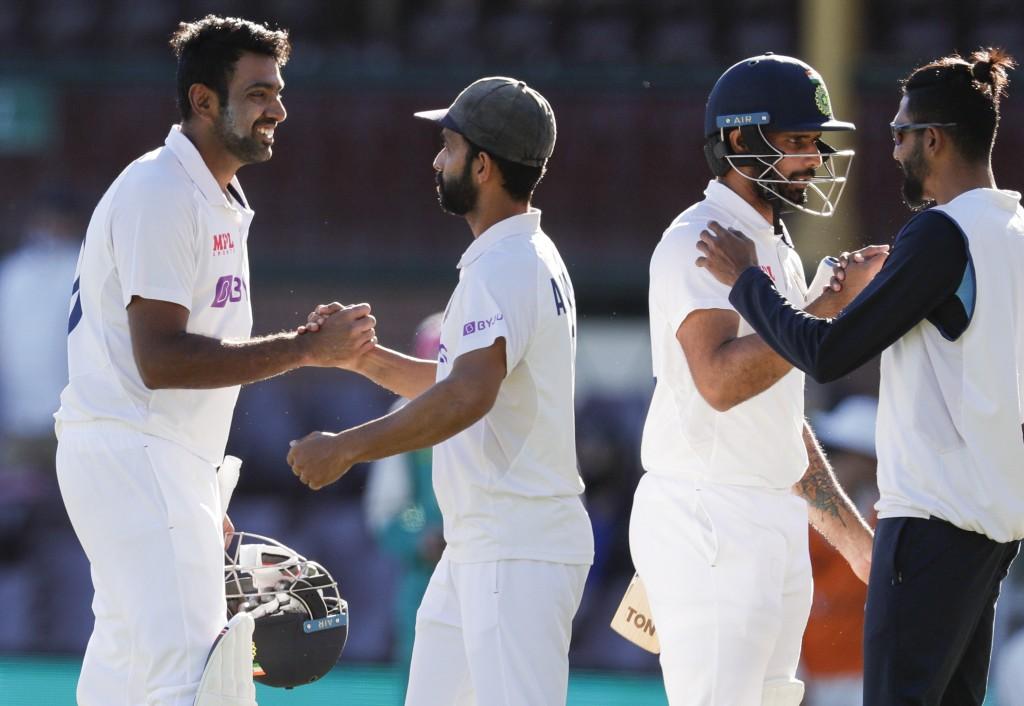 India's Ravichandran Ashwin, left, is congratulated by his captain Ajinkya Rahane as Hanuma Vihari is congratulated by teammate Mohammed Siraj, right,...