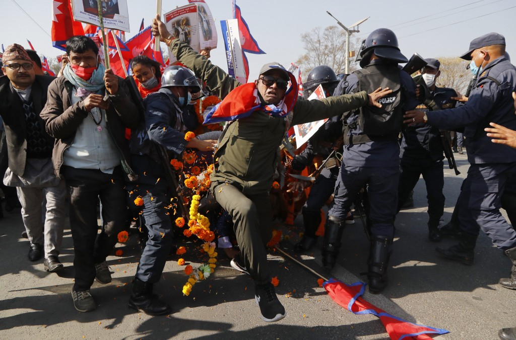 Pro-king supporters clash with riot police as they march demanding reinstating monarchy that was abolished more than a decade ago in Kathmandu, Nepal,...
