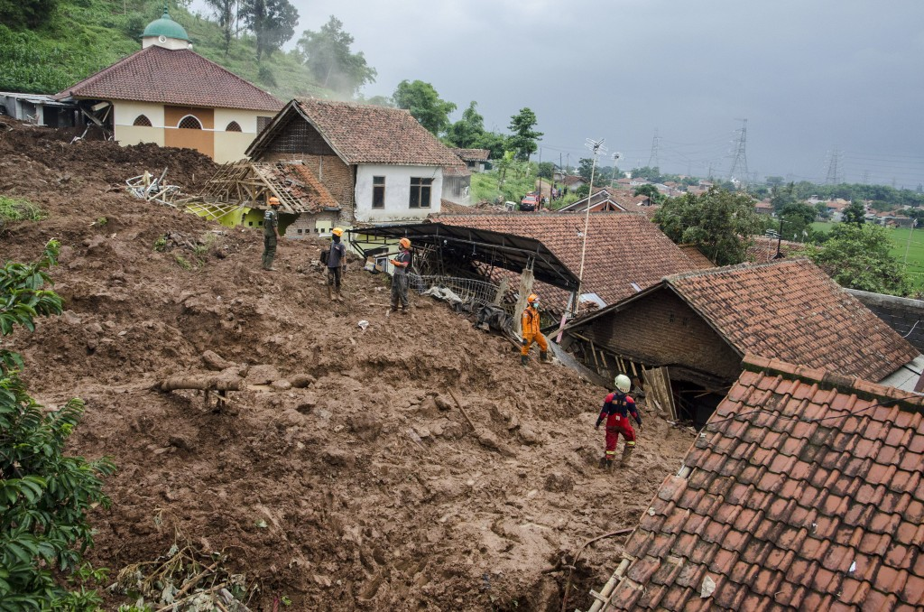 Rescuers search for victims at a village hit by Sunday's landslides in Sumedang, West Java, Indonesia, Monday, Jan. 11, 2021. Landslides triggered by ...