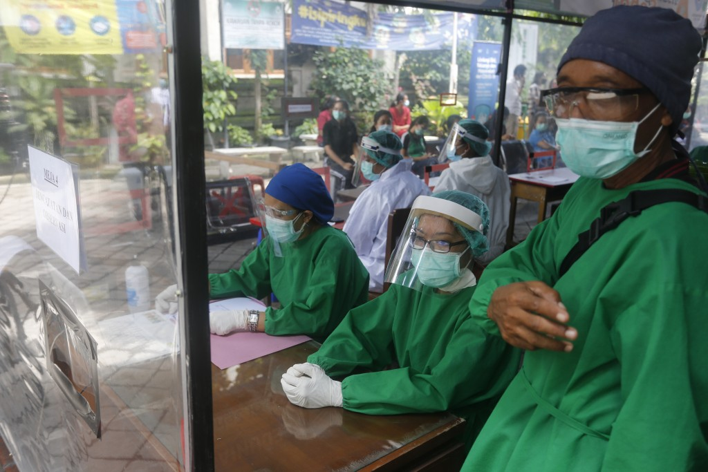 Health workers in a protective suit prepare for a coronavirus vaccine drill in Bali, Indonesia on Monday, Jan. 11, 2021. Indonesia's highest Islamic b...