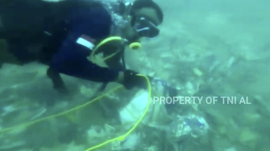 In this image made from undated video released by Indonesian Navy (TNI AL), divers is seen recovering debris strewn on the sea floor in Java Sea where...