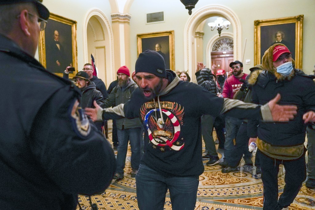 FILE - In this Jan. 6, 2021, file photo, Trump supporters gesture to U.S. Capitol Police in the hallway outside of the Senate chamber at the Capitol i...