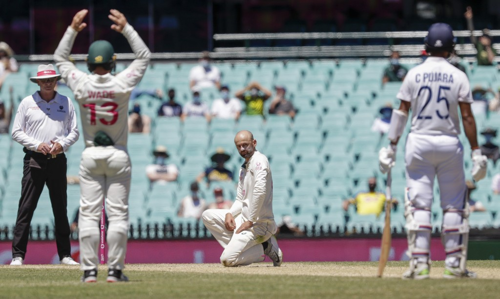 Australia's Nathan Lyon reacts after an appeal for LBW against India's Cheteshwar Pujara, right, is rejected during play on the final day of the third...