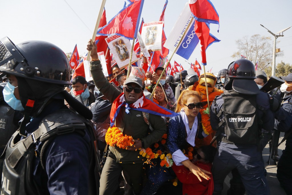 Pro-king supporters are stopped by riot police as they march demanding reinstating monarchy that was abolished more than a decade ago in Kathmandu, Ne...