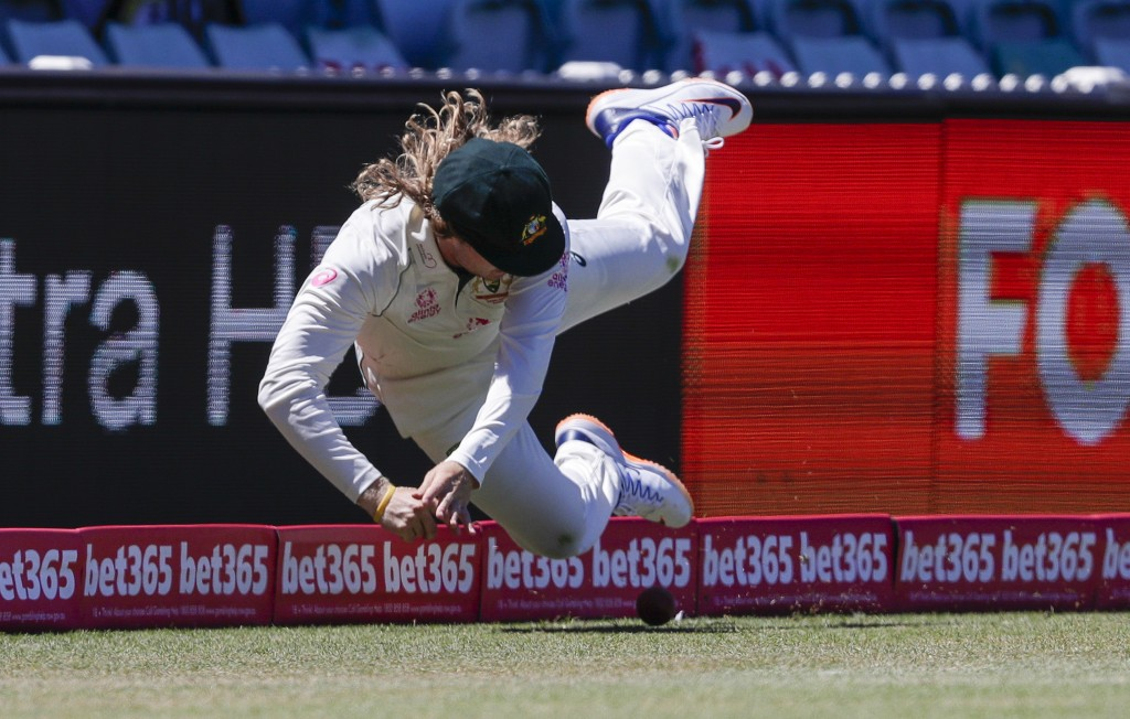 Australia's Will Pucovski is airborne as he fields the ball during play on the final day of the third cricket test between India and Australia at the ...