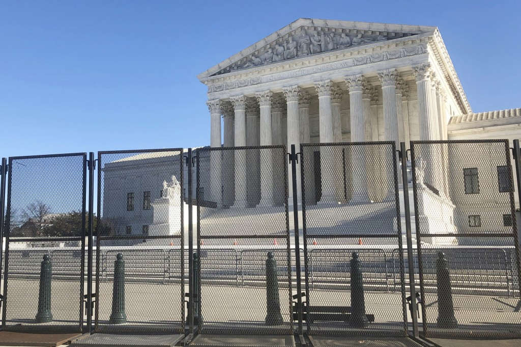 Anti-scaling fencing has been placed in front of the Supreme Court, which stands across the street from the U.S. Capitol, Sunday, Jan. 10, 2021, in Wa...