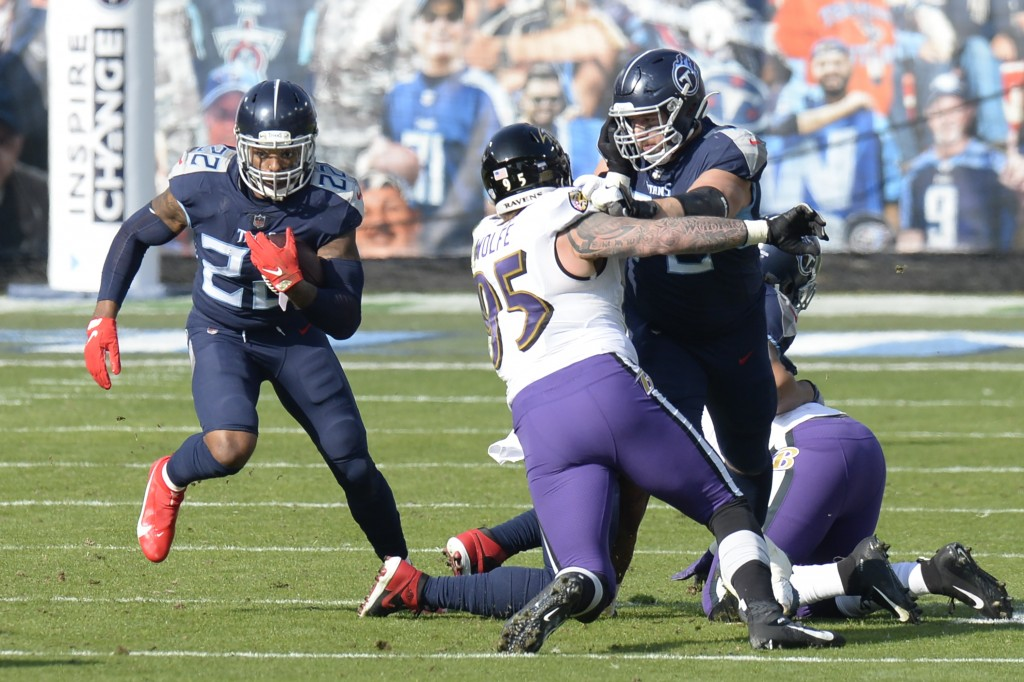 Tennessee Titans running back Derrick Henry (22) carries the ball past Baltimore Ravens defensive end Derek Wolfe (95) in the first half of an NFL wil...