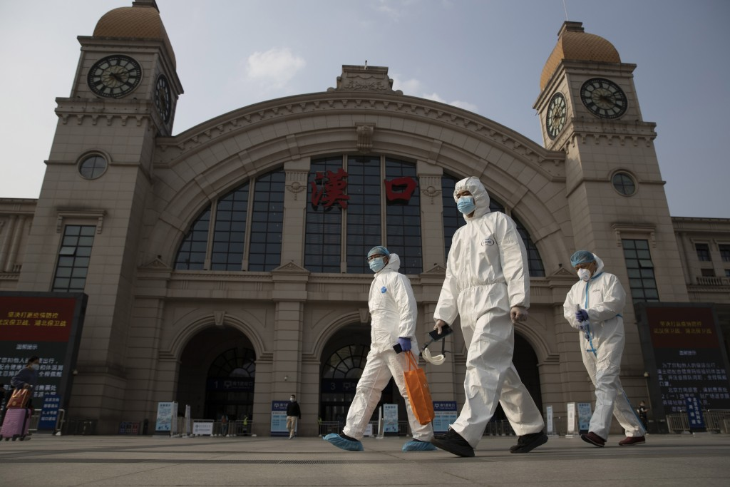 FILE - In this April 7, 2020, file photo, workers in protective suits walk past the Hankou railway station on the eve of its resuming outbound traffic...