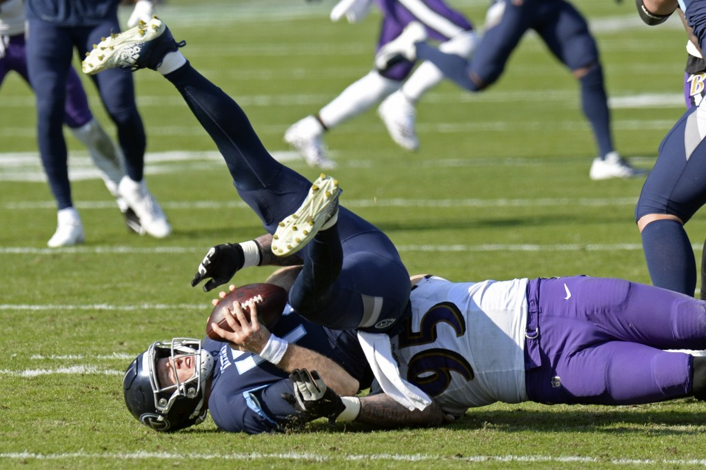 Tennessee Titans quarterback Ryan Tannehill (17) is sacked by Baltimore Ravens defensive end Derek Wolfe (95) for a 7-yard loss in the first half of a...