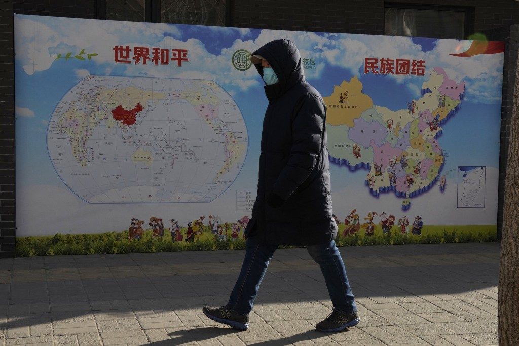 """A man walks past a poster with the slogans """"World Peace"""" and """"Ethnic Unity"""" in Beijing, China Monday, Jan. 11, 2021. A Chinese official on Monday deni..."""