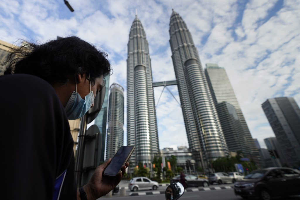 A man wearing a face mask listens to live broadcast in front of Twin Towers in downtown Kuala Lumpur, Malaysia, Monday, Jan. 11, 2021. Prime Minister ...