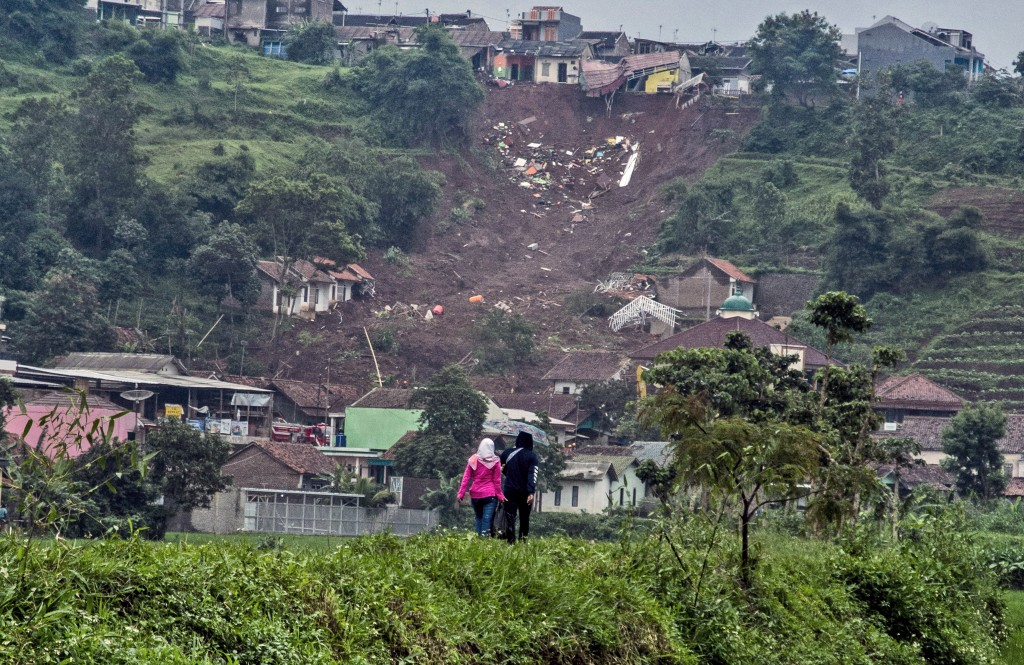 People walk past the site where a village was hit by landslides on Sunday, in Sumedang, West Java, Indonesia, Monday, Jan. 11, 2021. Landslides trigge...