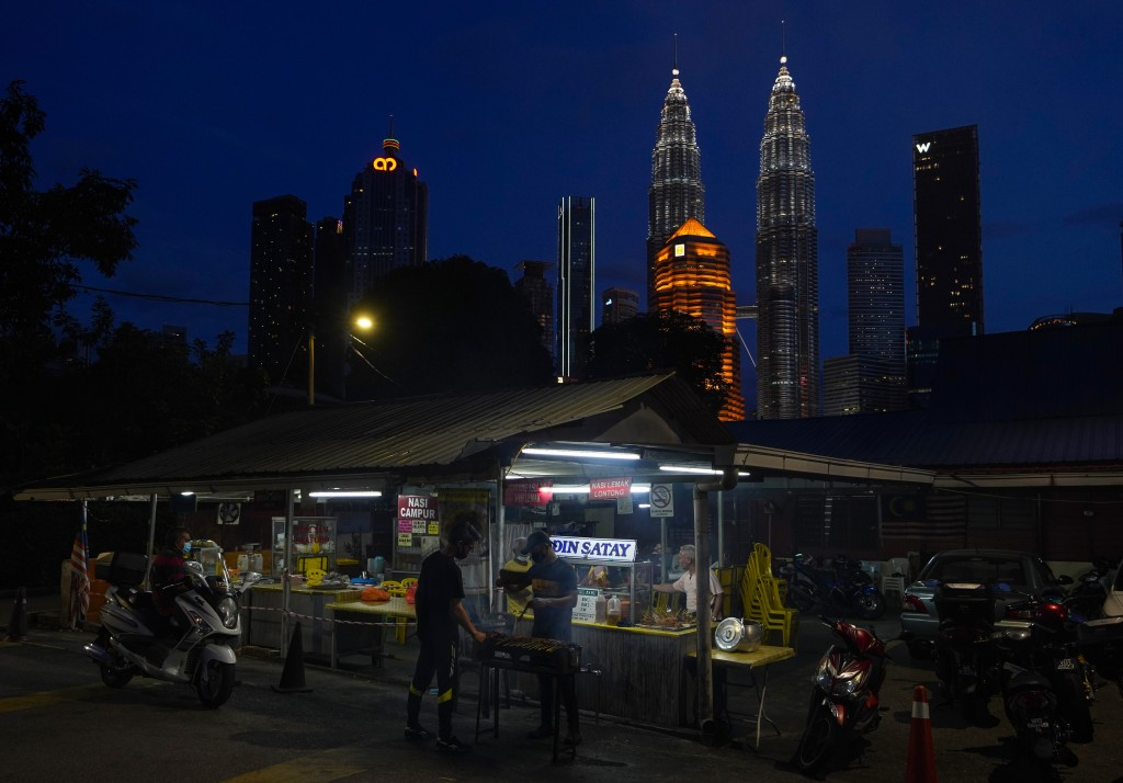 A local food vendor prepares food with the Twin Towers in downtown Kuala Lumpur in the background background, Malaysia, Monday, Jan. 11, 2021. Prime M...