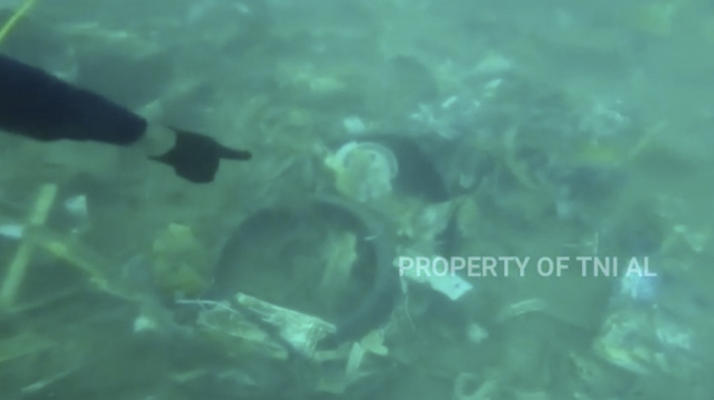 In this image made from undated video released by Indonesian Navy (TNI AL), divers points at debris strewn on the sea floor in Java Sea where Sriwijay...