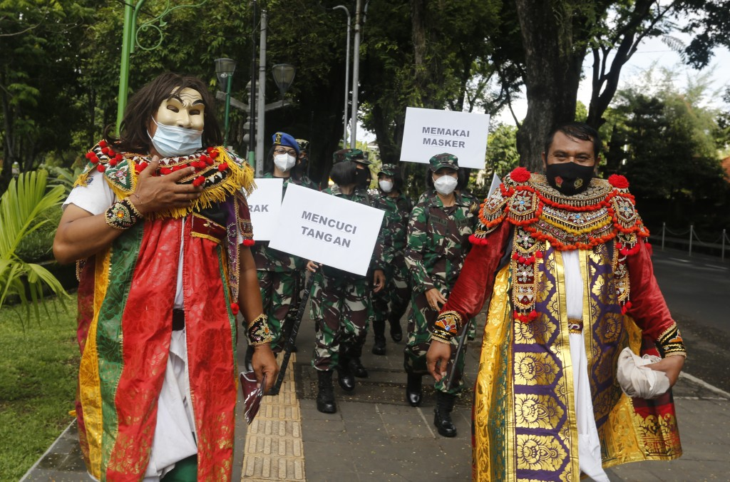 Indonesian military officers wear traditional Balinese costume calling for people to always have their mask and wash hands to prevent the spread of co...