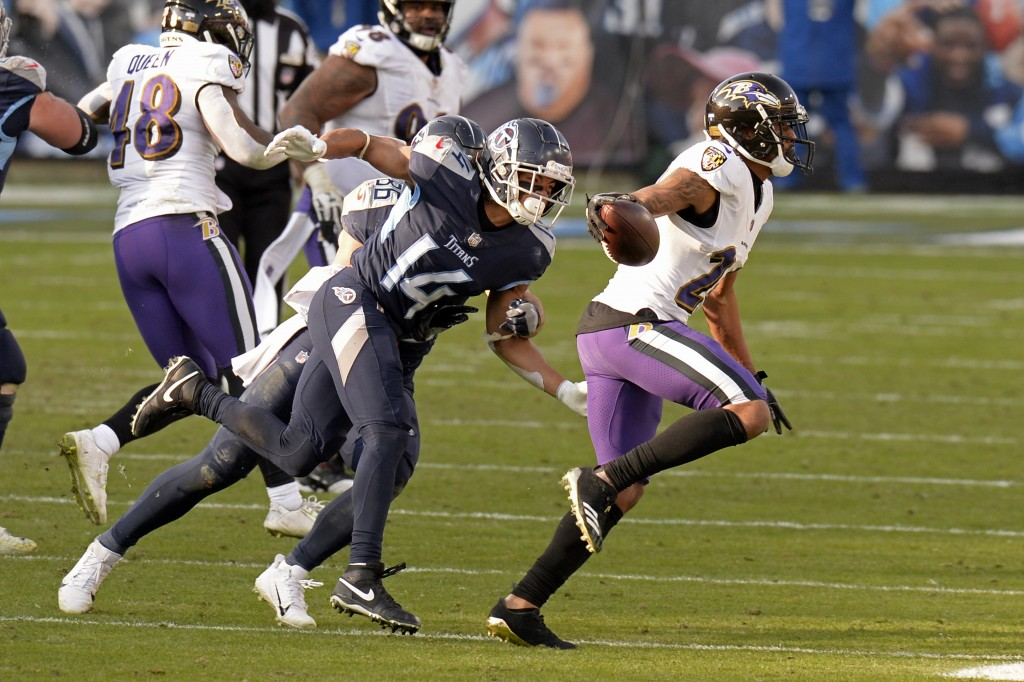 Baltimore Ravens cornerback Marcus Peters (24) is chased by Tennessee Titans wide receiver Kalif Raymond (14) after Peters intercepted a pass late in ...