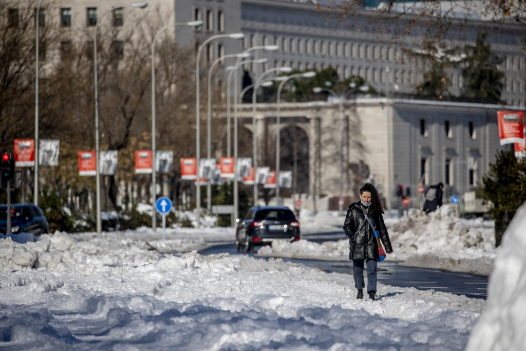 A woman walks along Paseo Castellana covered with the snow in Madrid, Spain, Monday, Jan. 11, 2021. The Spanish capital is trying to get back on its f...