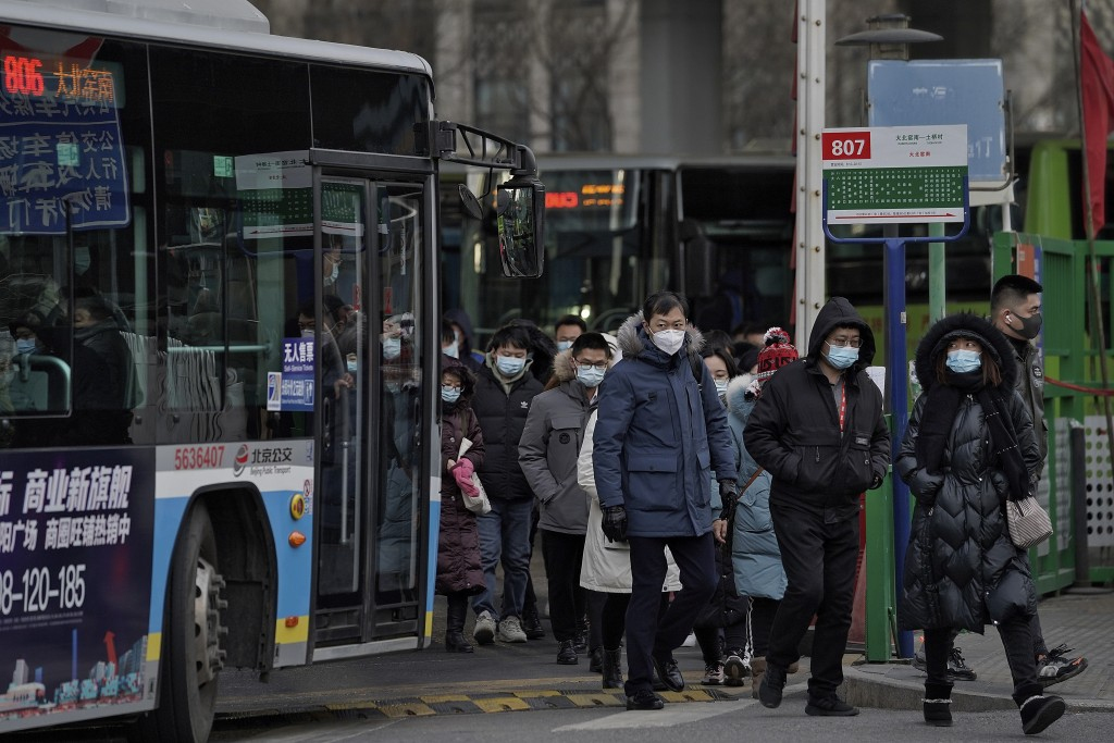 People wearing face masks to help curb the spread of the coronavirus walk out from a bus station for the traveller from the outskirts of Beijing on Mo...