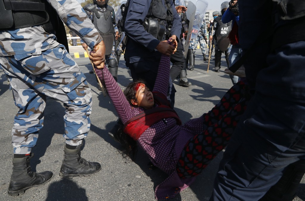 A pro-king supporter injured during clash with riot police is carried away as they march demanding reinstating monarchy that was abolished more than a...