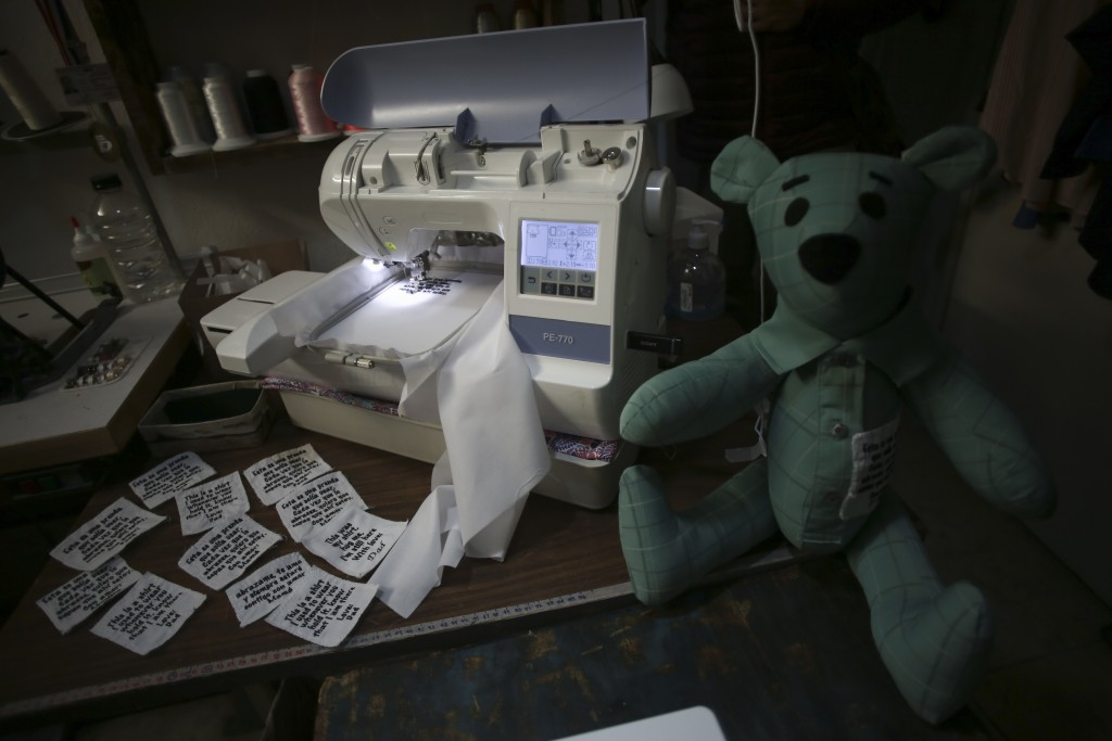 Tags ready to be sewn onto bears for people who lost a loved one to COVID-19, made out of one of the deceased's articles of clothing, sit beside a sew...