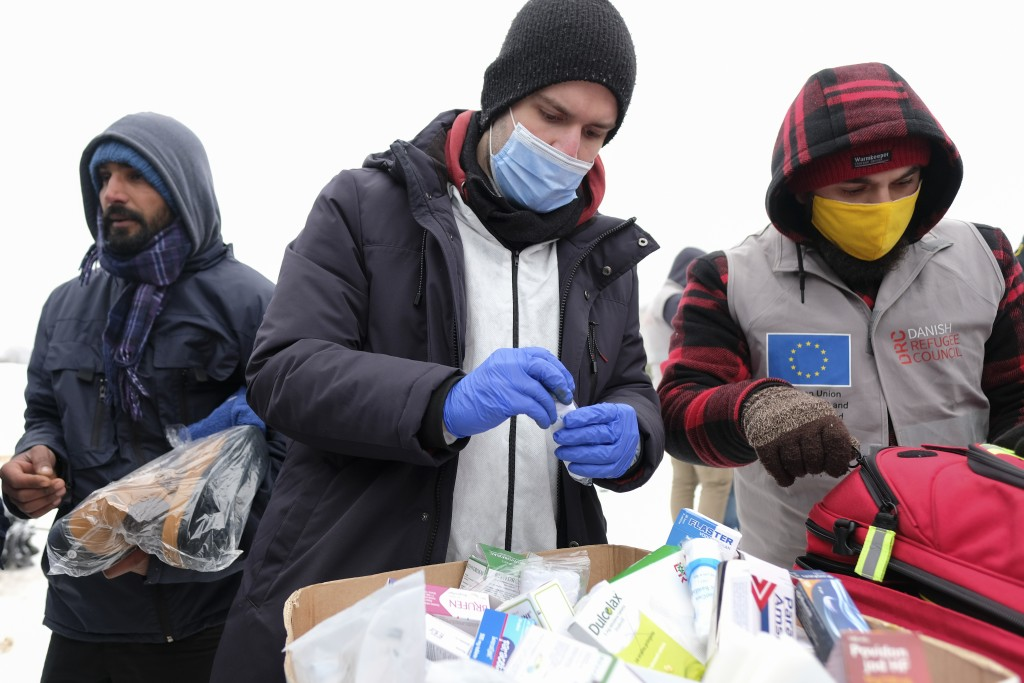 Medical staff examine migrants at the Lipa camp, outside Bihac, Bosnia, Monday, Jan. 11, 2021. Aid workers say migrants staying at a camp in northwest...