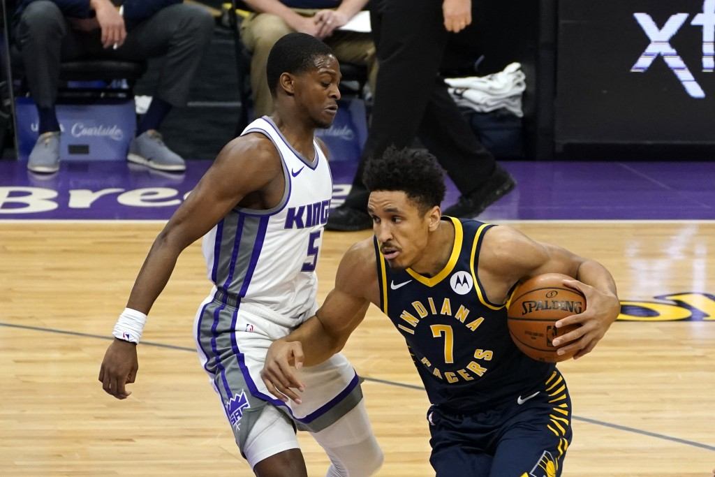 Indiana Pacers guard Malcolm Brogdon, right, drives against Sacramento Kings guard De'Aaron Fox during the first half of an NBA basketball game in Sac...