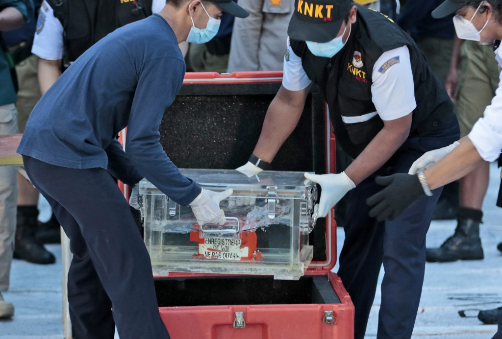 Members of National Transportation Safety Committee place a box containing the flight data recorder of Sriwijaya Air flight SJ-182 retrieved from the ...