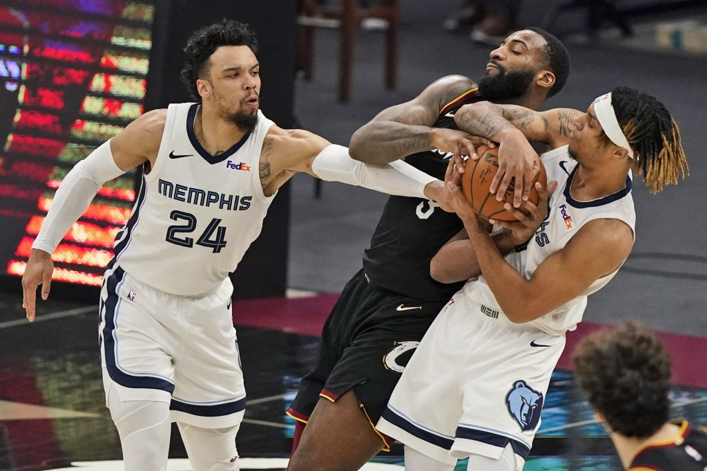 Cleveland Cavaliers' Andre Drummond, center, battles for the ball with Memphis Grizzlies' Dillon Brooks, left, and Brandon Clarke in the second half o...