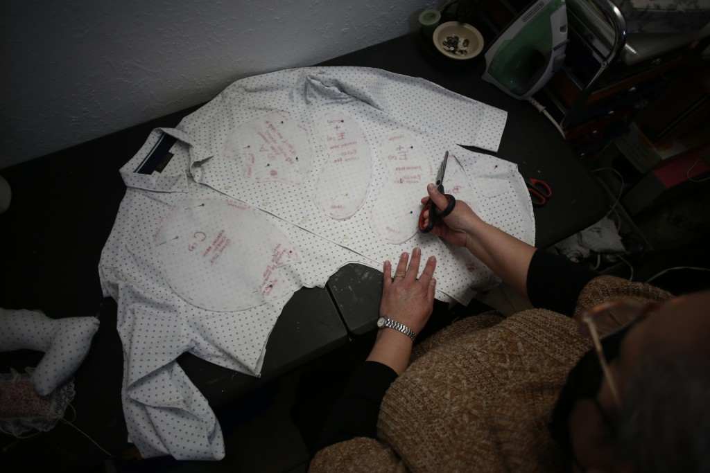 Erendira Guerrero cuts pieces from the shirt of a person who died of COVID-19 as she makes a stuffed bear for one of the deceased's relatives, at her ...