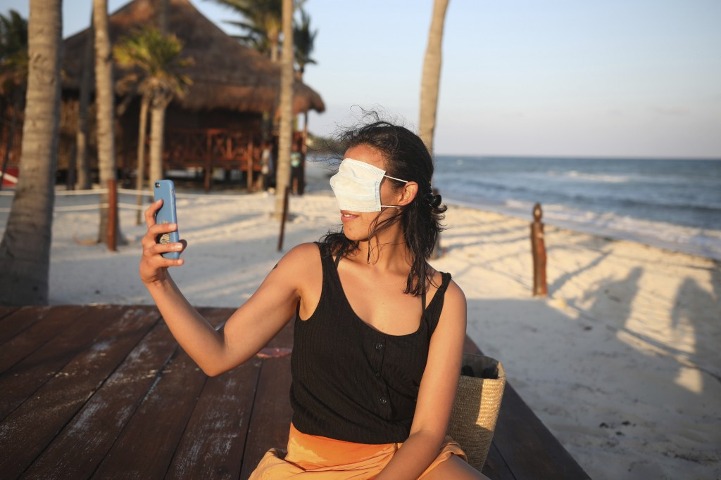 Mexico City resident Romina Montoya takes a playful selfie wearing a protective face mask over her eyes and nose, in Playa del Carmen, Quintana Roo st...