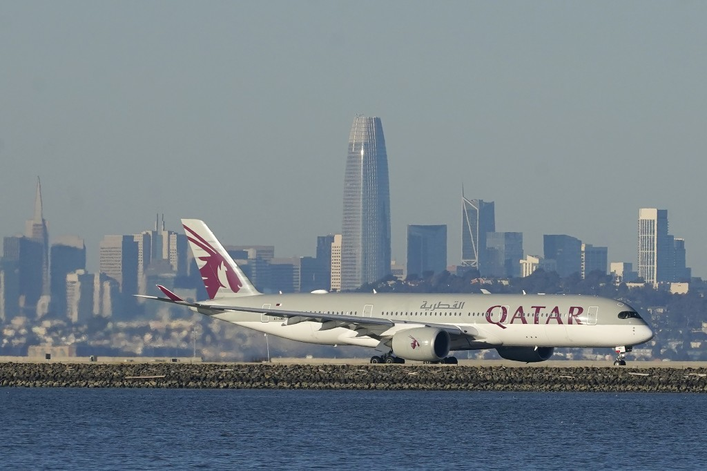 FILE - In this Dec. 22, 2020 file photo, a Qatar Airways plane prepares to take off at San Francisco International Airport during the coronavirus pand...