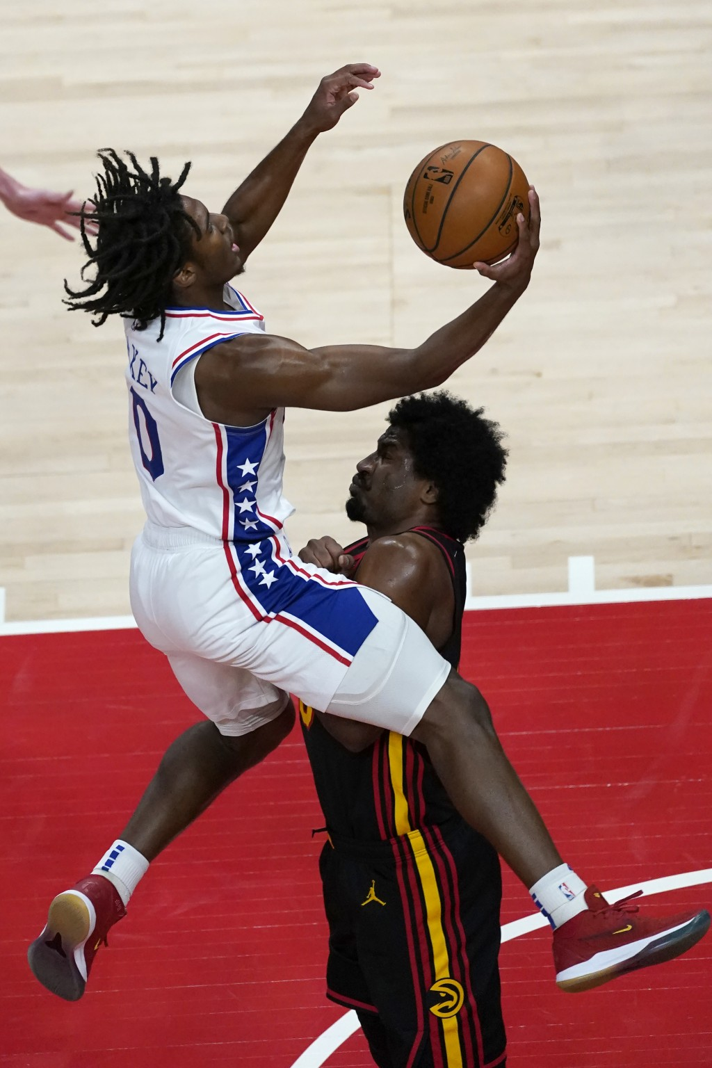 Philadelphia 76ers guard Tyrese Maxey (0) is fouled by Atlanta Hawks forward Solomon Hill (18) as he drives to the basket during the first half of an ...