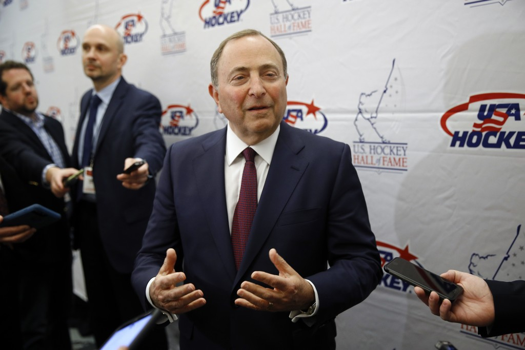 FILE - NHL Commissioner Gary Bettman speaks with members of the media before being inducted into the U.S. Hockey Hall of Fame in Washington, in this T...