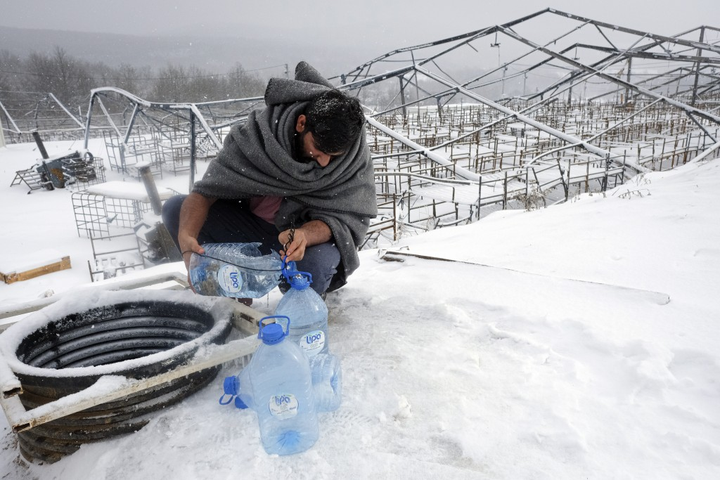 A migrant uses plastic bottles to take water out of a well during a snowfall at the Lipa camp, outside Bihac, Bosnia, Monday, Jan. 11, 2021. Aid worke...