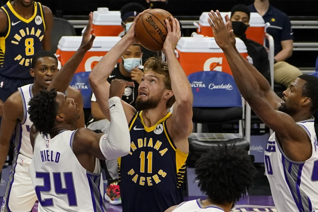 Indiana Pacers forward Domantas Sabonis, center, goes to the basket between Sacramento Kings' Buddy Hield, left, and Harrison Barnes, right, during th...