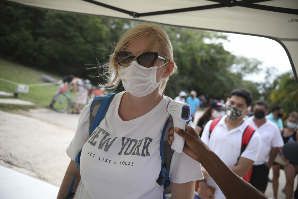 A tourist, wearing a protective face mask, stands still as an employee measures her body temperature as a preventive measure amid the new coronavirus ...