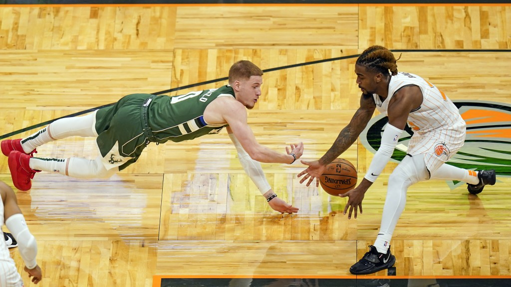 Milwaukee Bucks guard Donte DiVincenzo, left, dives for a loose ball against Orlando Magic guard Jordan Bone, right, during the second half of an NBA ...