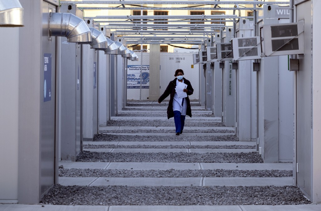 FILE - In this Sunday, Jan. 10, 2021, file photo, a health care worker walks across the facility at a New York Health and Hospitals vaccine clinic in ...