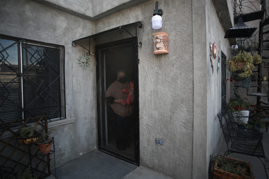 Erendira Guerrero stands at the door of her home, holding one of the stuffed bears she makes for people who lost a family member to COVID-19, using on...