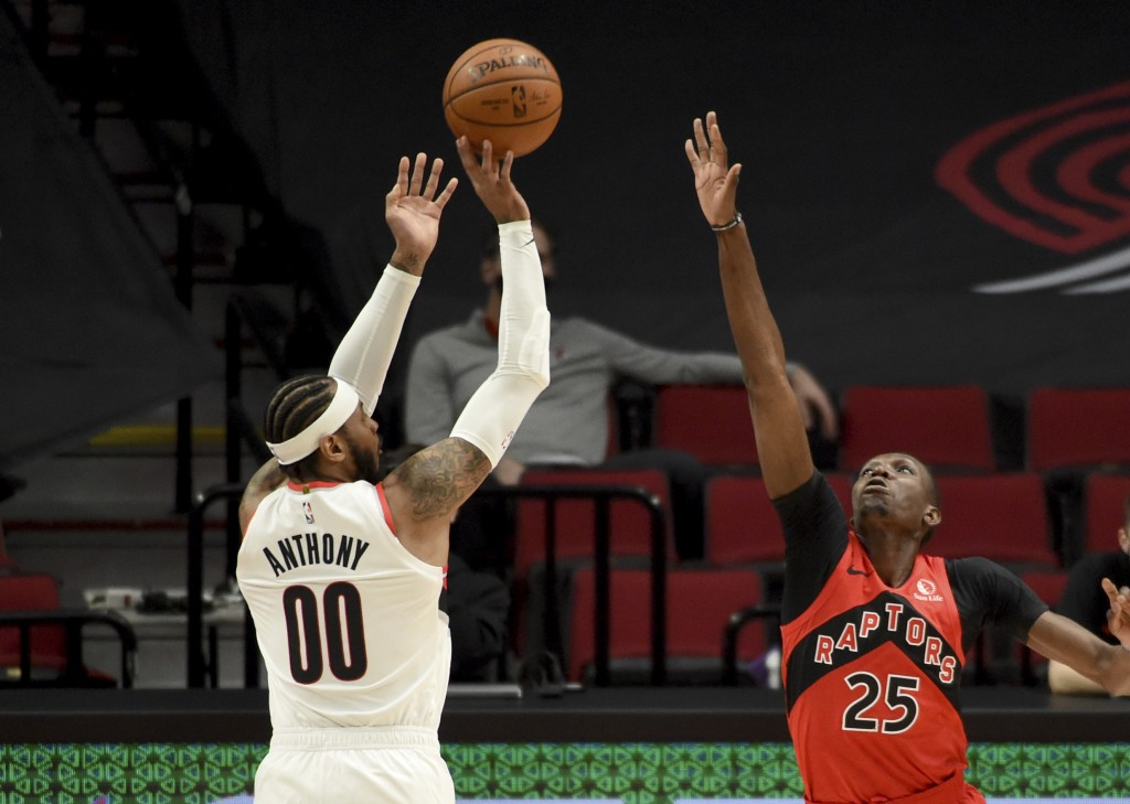 Portland Trail Blazers forward Carmelo Anthony, left, hits a basket over Toronto Raptors forward Chris Boucher, right, during the first half of an NBA...