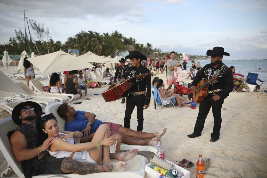 """Roving musicians """"Los Compas"""" approach a group of tourists on the shore of Mamitas beach, in Playa del Carmen, Quintana Roo state, Mexico, Tuesday, Ja..."""