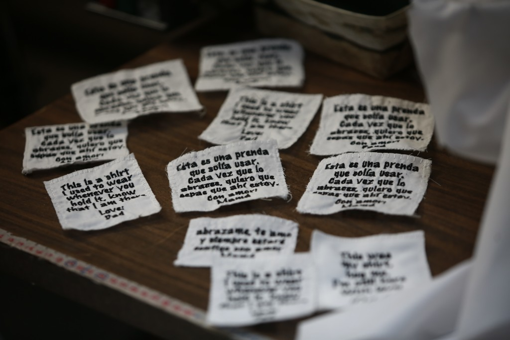 Tags ready to be sewn onto bears made for people who lost a loved one to COVID-19, out of one of the deceased's articles of clothing, sit beside a sew...