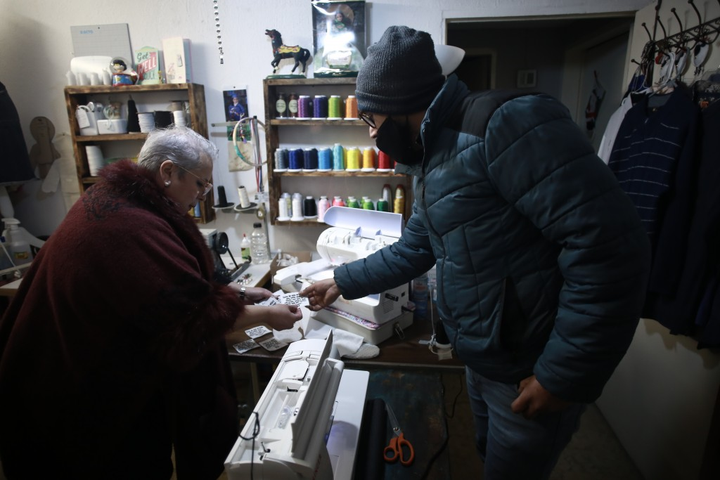 Jaime Walfre Aguilar Martinez, whose 50-year-old father died of COVID-19 in November, picks out a tag to have sewn onto the stuffed bear that Erendira...