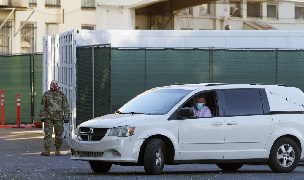 A member of the California National Guard stands next to refrigerated trailers as a funeral hearse driver exits the department of the Los Angeles Coun...
