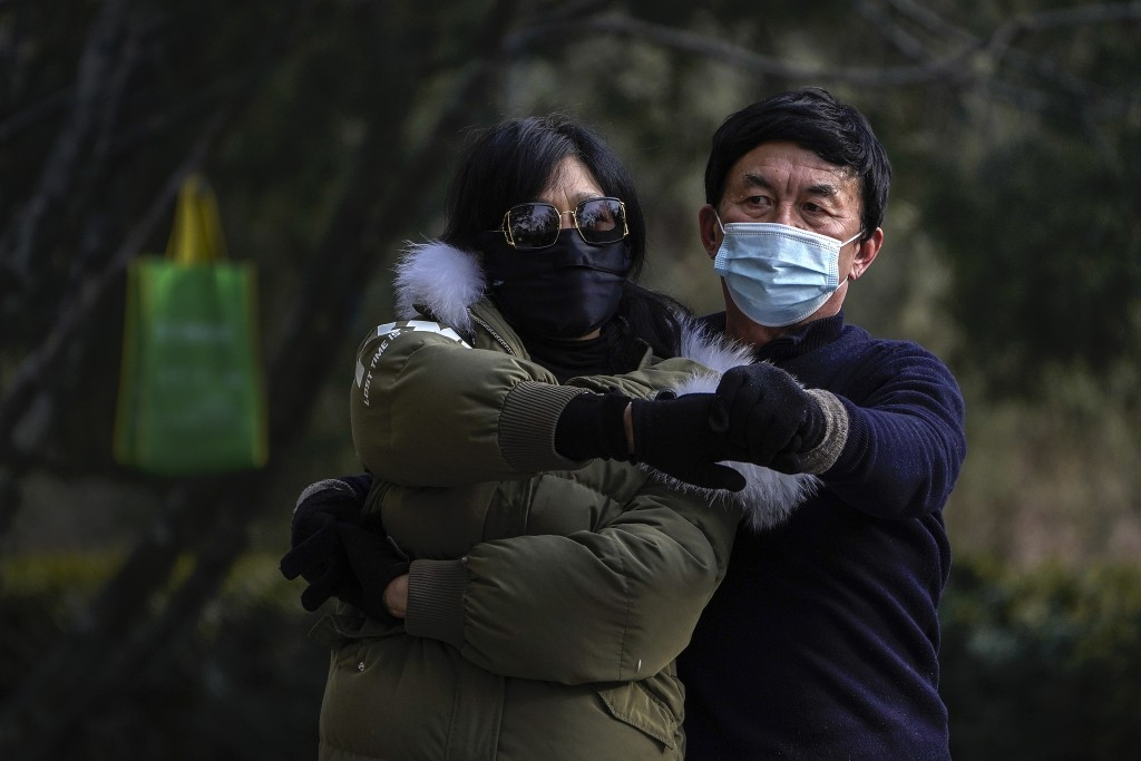People wearing face masks to help curb the spread of the coronavirus, practice a social dance at a public park in Beijing, Tuesday, Jan. 12, 2021. Loc...