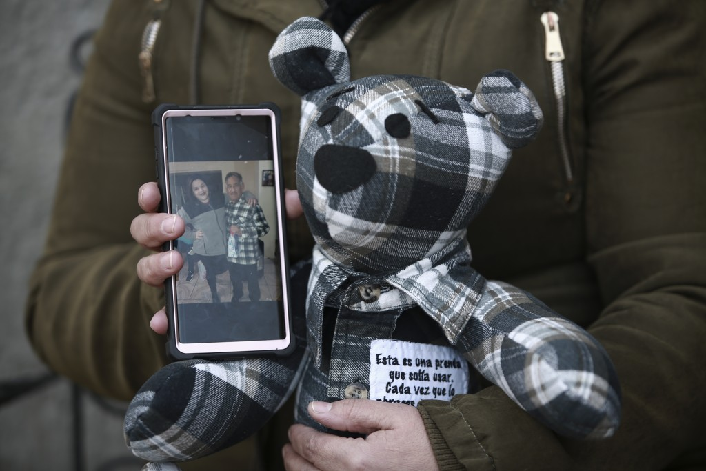 Araceli Ramirez shows a stuffed bear she had made from the shirt of her father, Lorenzo Ramirez, who died so quickly from COVID-19 two months ago that...