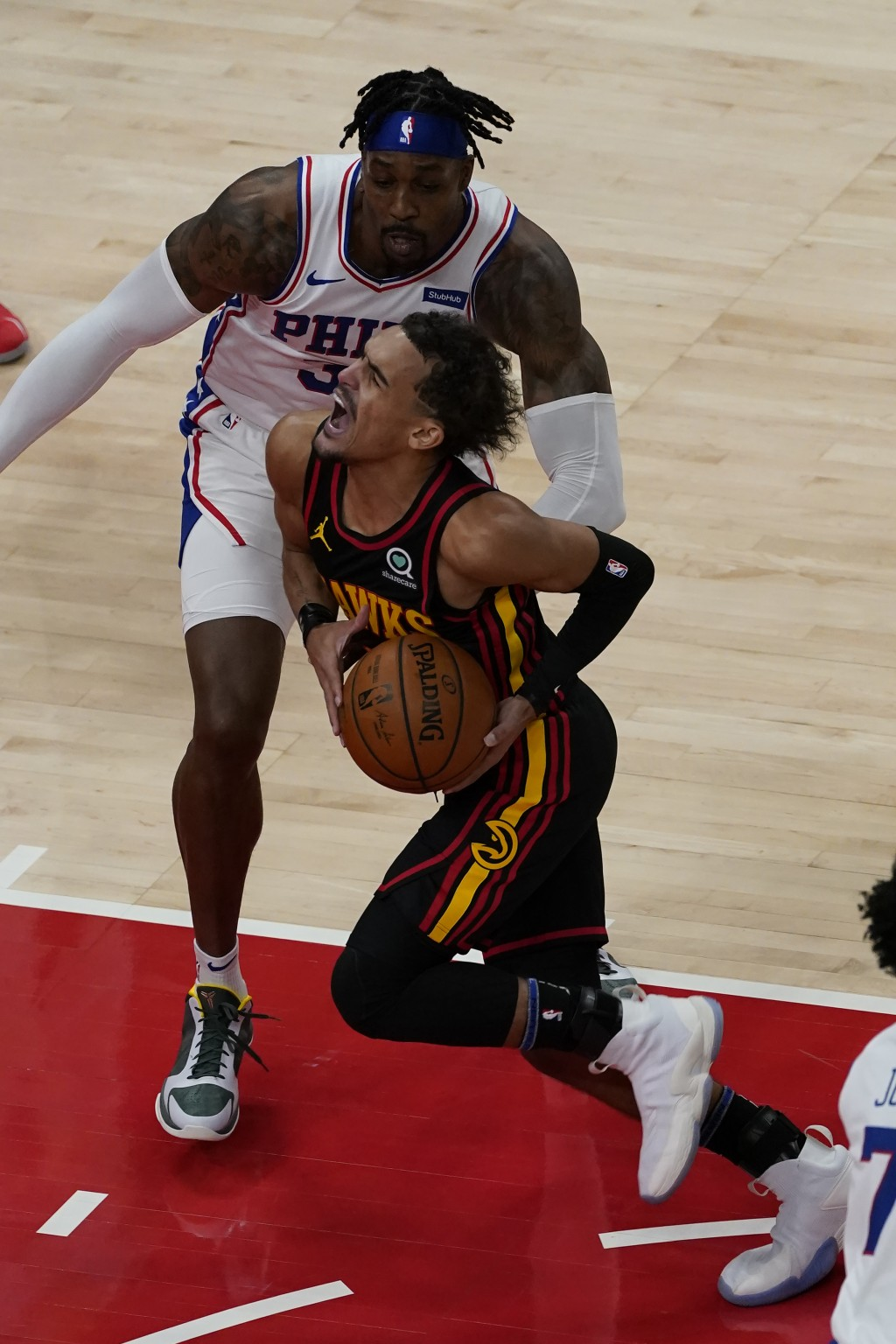 Atlanta Hawks guard Trae Young (11) drives against Philadelphia 76ers center Dwight Howard (39) during the first half of an NBA basketball game Monday...