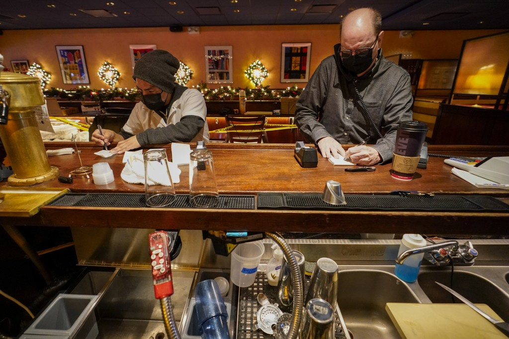 Steve Olsen, right, owner of the West Bank Café and Segundo Agueza take to-go orders over the phone in the empty restaurant, Saturday, Jan. 9, 2021, i...