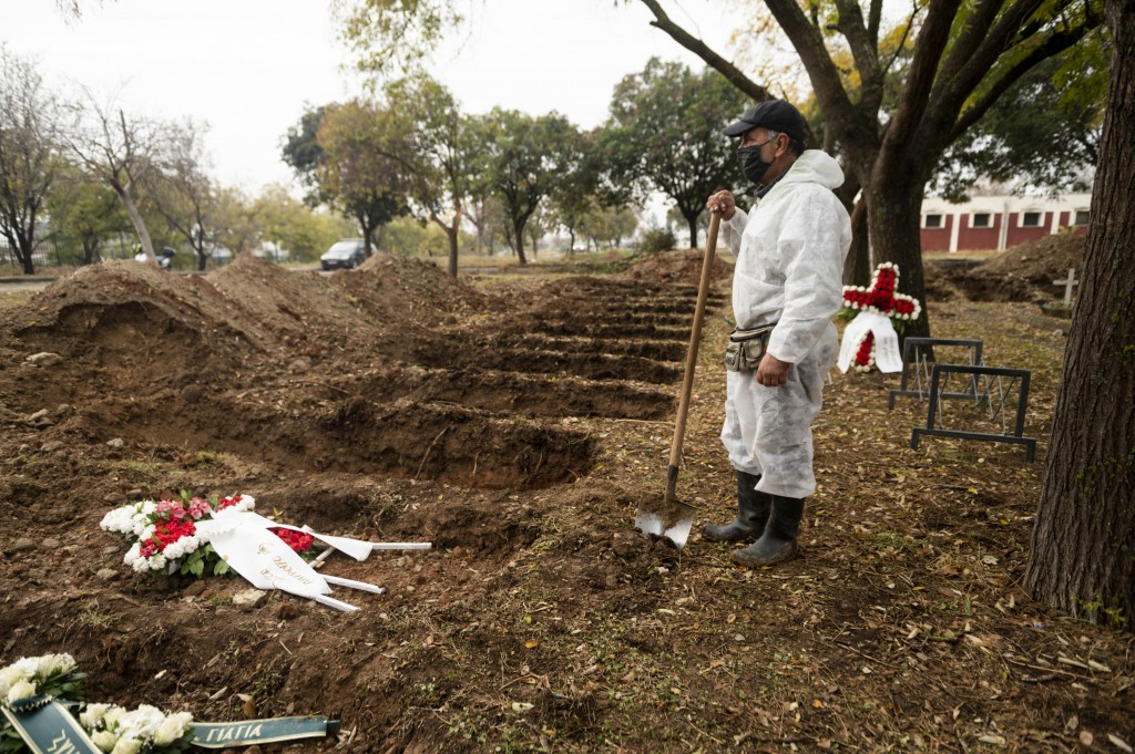 A worker stands over graves during a funeral ceremony for a person who died of COVID-19, in the northern city of Thessaloniki, Greece, Saturday, Dec. ...